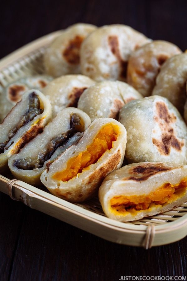 A bamboo tray containing Oyaki, Japanese dumplings with kaboch and miso eggplant fillings.