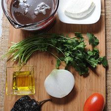 3 tazas de frijoles negros cocidos 10 ramas de cilantro sal al gusto 3 cucharadas de aceite de oliva 100 gramos de queso panela 1 pieza de chile ancho 1 pieza de jitomate guaje 1 pieza de diente de ajo 1/2 pieza de cebolla blanca