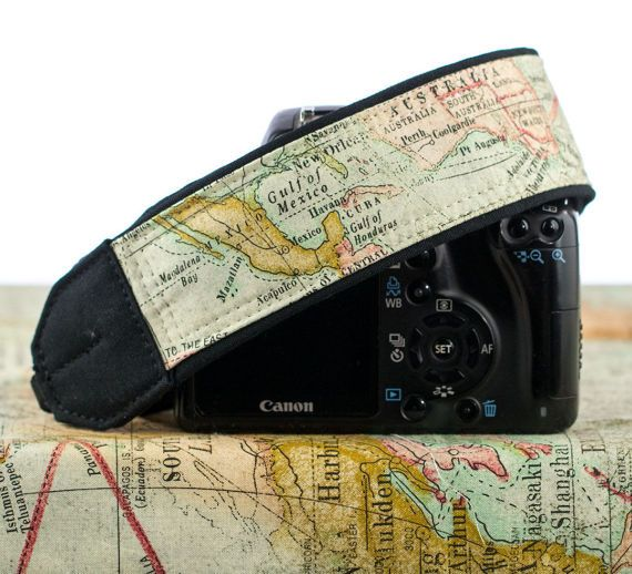 dSLR camera strap featuring an old world map with subdued colors including, mint green, gold and coral with a light aqua background. The map depicted on this fabric is NOT true to life as it is a collage of different sections of the world, mainly Asia, Australia, US/Canada and lots of ocean. Europe is not shown. Many people have requested particular countries or areas and although I do try to honor these requests when possible not all requests are possible. Due to the random design on th...