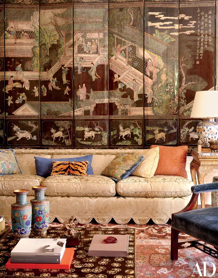In the living room, a Coromandel screen is mounted behind a banquette upholstered in a Claremont damask; the lacquer low tables are inlaid with mother-of-pearl.