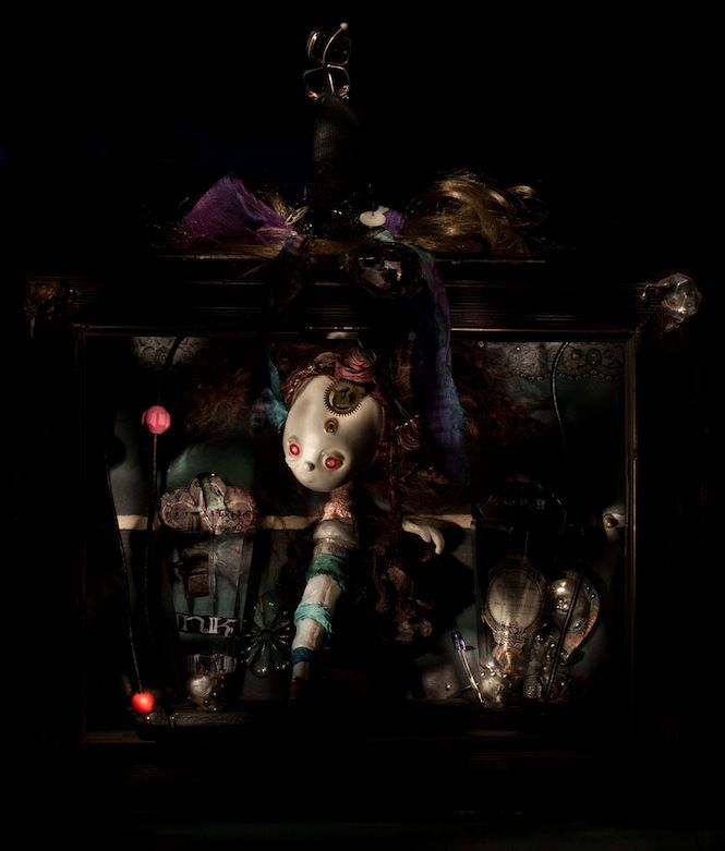 Illusion of time (Mona Mae) - OOAK artwork captured in still life torchlight photo - work itself uses mix of materials - porcelain clay, glass eyes, fabric for dolls, metal parts made by artist - background as glass, fusing, metal work, soldered pieces, etc., etc.