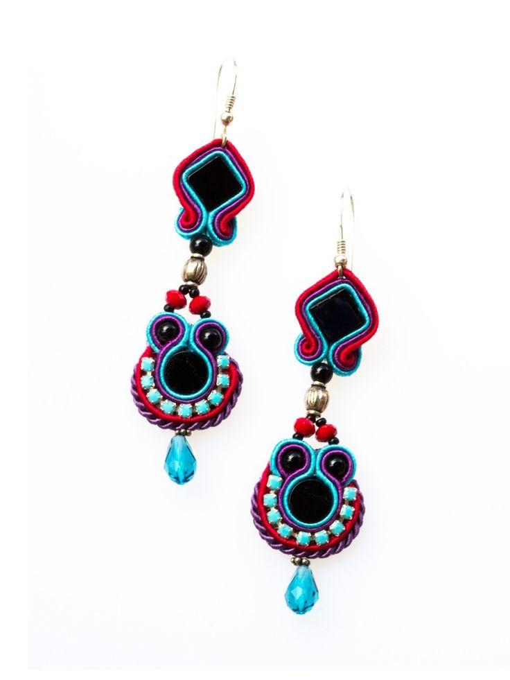 Aztec- Oryginalne kolczyki w stylu boho. Czarne onyksy otoczone turkusową taśmą cyrkoniową wtopione zostały w czerwone, niebieskie i fioletowe sznurki soutache. Całość zdobią kryształki Swarovskiego i srebrne, oksydowane elementy. Kolczyki zostały wykończone ekologiczną zamszową skórką i zaimpregnowane. Bigle srebrne.