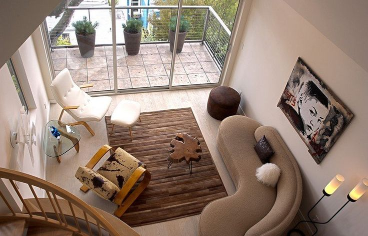 canapé demi lune beige, tapis rectangulaire marron et un fauteuil blanc comme accent dans le petit salon