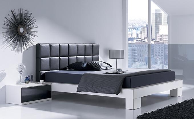 Habitación de matrimonio vanguardista con cabezal tapizado en negro.