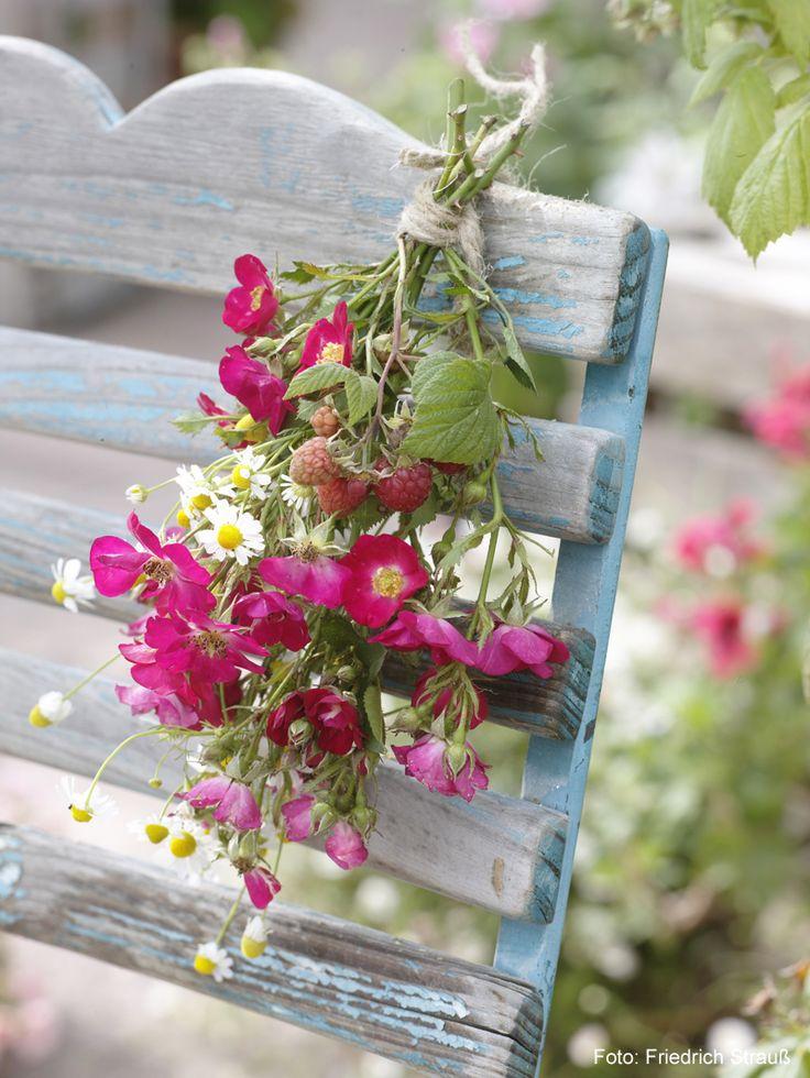 Kleiner Strauß aus Rose, Kamille und Himbeerranke, der an der Rückenlehen eines Gartenstuhls befestigt ist