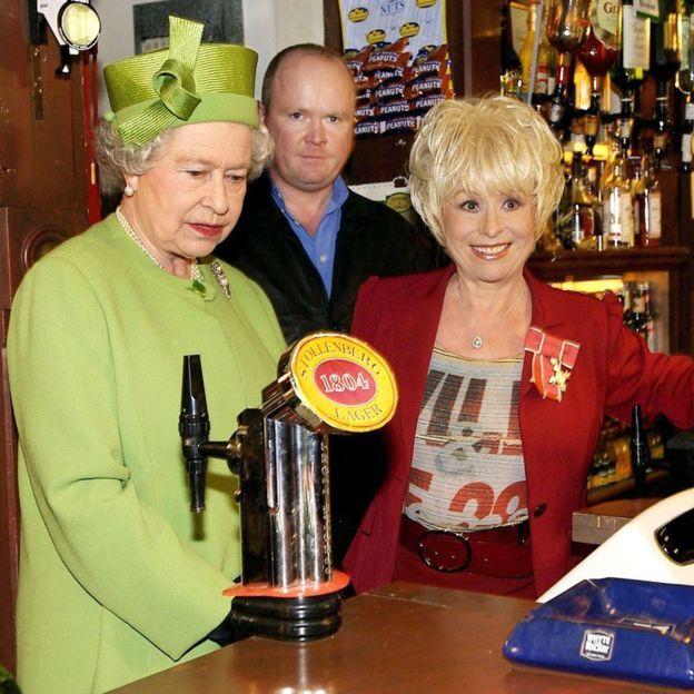 Queen Elizabeth II in the Queen Vic pub during a visit to Elstree Studios where EastEnders is filmed in 2001.