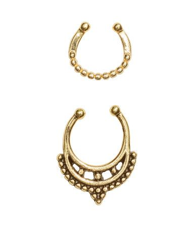 Thin metal nose rings in different sizes and designs to fit wearers without a hole in the nose. Adjustable size.