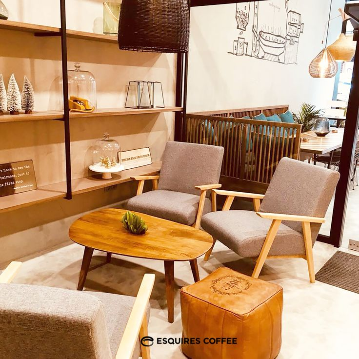 ESQUIRES COFFEE PORTO _ Lounge seating area #woodentable #coffeetable #mid-century #woodenchair #ottoman #concretewall #concretefloor #industrialshelf #woodenshelf #coffeeshop #coffeeshopporto #esquirescoffee #porto #portugal