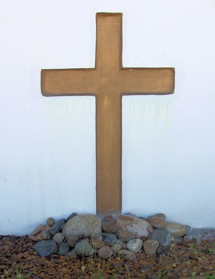 """Cross 1:  brown painted cross on a white wall, with a pile of rocks at its foot.  Quarter Page size 1275 x 1650px (300ppi); prints at 4.25 x 5.5""""."""