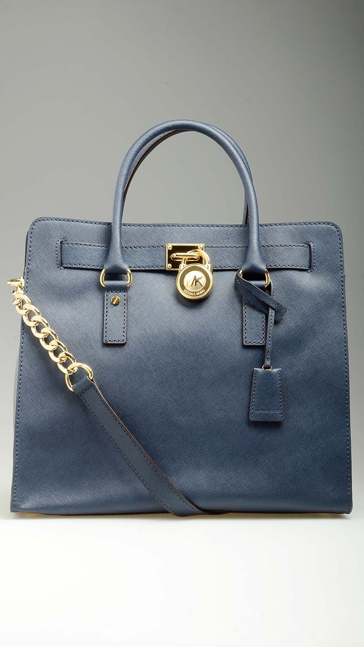 Golden chains crossbody strap embellished big size blue Hamilton tote bag characterized by top flap snap closure, tote handles, a zippered central compartment, monogram lining, four inner open pockets and a zippered one, protective studs, padlock front detailing, golden hardware, 14.3'' x 5.5'' x 10.6'', 100% Saffiano leather.