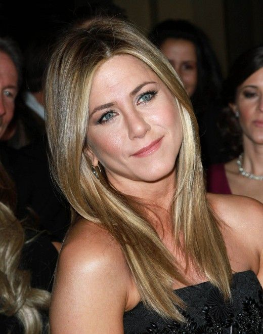 Jennifer Aniston with medium ash blonde hair, center parted, long, and straight. Celebrities with medium ash blonde hair.