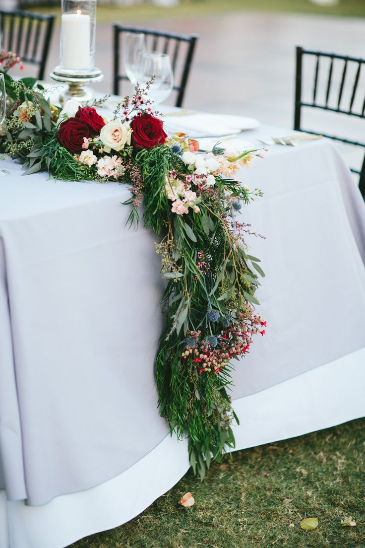 detail of garland spilling over the ends of the wedding head table features red roses, white roses, peach stock, blue thistle, pink wax flower, raintree pods, bleeding heart vine peppered in a mix of eucalyptus and weeping popocarpus greenery. mercury glass pillars and candles added elegance