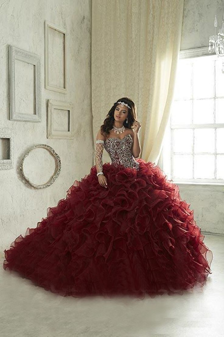 The intricately beaded bodice of this House of Wu 26833 organza quinceanera dress showcases a strapless sweetheart neckline, basque waist and lace-up back. Scattered rhinestones accent the wire edged ruffles adorning the ball gown skirt and sweep train.