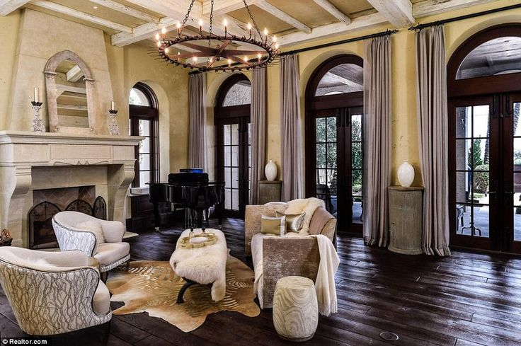 The property is decorated in a Mediterranean Revival style, featuring stone fireplaces, medieval chandeliers and tall windows