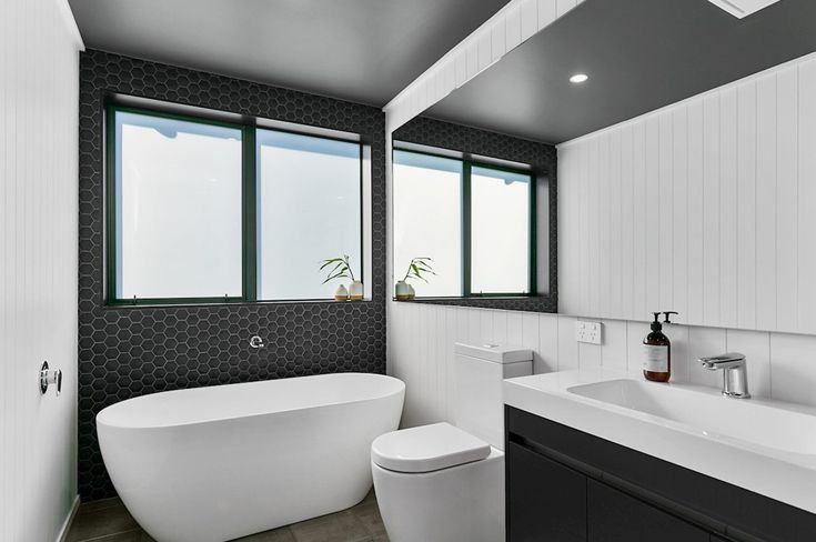 If you're working with a smaller area, think about a larger mirror. This modern new bathroom maximises the sense of space with a mirror that reflects the tall vertical lines of the HardieGroove wall. It's a look that's very on trend right now, and you can see why! It's crisp and clean, and makes any space look twice the size!  #jameshardie #hardiehomes #homeinspiration #hardiegroove #interiordesign #bathrooms #moderndesign