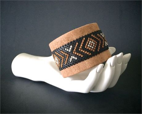 leather cuff bracelet for women or men with a cross-stitch geometric tribal design in dark gold and cream embroidery thread. piece fits best on the forearm for those ladies with slimmer arms. cuff made with two different types of leather, cross stitch floss, and a sam brown button stud.  leather boho jewelry constructed from a natural distressed leather base with burnished edges, and has a black perforated leather upper. i took advantage of the perforation in the upper leather to use as a…