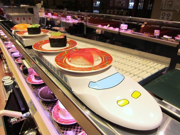 a new trend in conveyer belt sushi restaurants in Tokyo -- order what you like and have it delivered to your seat by train or dragon!