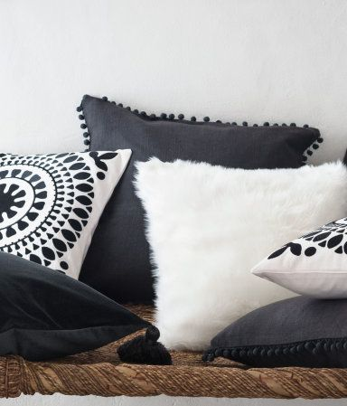 Cushion cover in woven cotton fabric with pompom trim at edges. Concealed zip.
