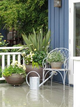 Create a welcoming cameo with planters at different heights, a chair and a watering can. Coordinate the colours to contrast with paintwork.