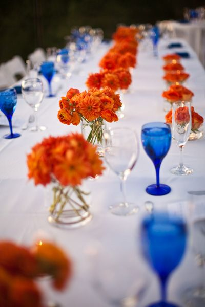Love the glass vases with bright orange flowers and blue wine glasses - R P Scissors Blog