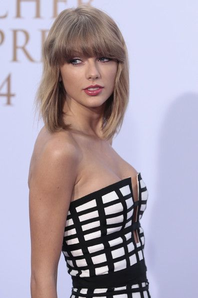 Taylor Swift looks like a red hot and sexy Sports Illustrated swimsuit model wearing her black and white strapless dress.