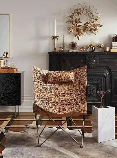 in the wings. Modern take on legendary design shelters with cocoon-like comfort. Brass frame's accordion shape supports a cheetah print hair-on-hide sling. Pair with matching headrest––a design detail we love.
