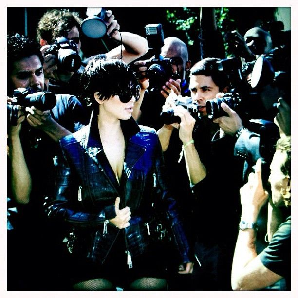 he Keeping Up With The Kardashians looks right at home in  a Kris Jenner-esque cropped wig, leather jacket, and sunglasses, surrounded by a host of thirsty paparazzi.   For Vogue Italy