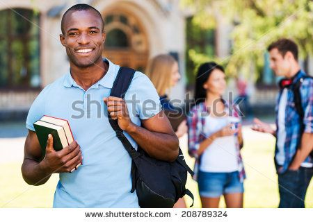 Enjoying university life. Handsome young African man holding books and smiling while standing against university with his friends chatting in the background  - stock photo