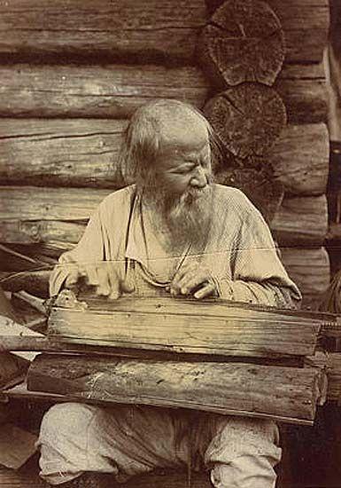 """Слепой музыкант, играющий на """"кандалэ"""" - род гуслей. Карелы. Фотоархив РЭМ"""