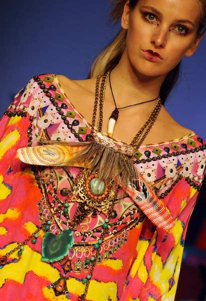 A model adorned with a boomerang necklace parades vividly coloured beachwear by 'Camilla' during Fashion Week Australia in Sydney on April 30, 2012.