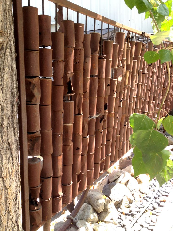 """ooooh ... I'm getting closer to figuring out what to do with all the tin cans I've been saving .... Rusted tin can """"bamboo"""" fence"""