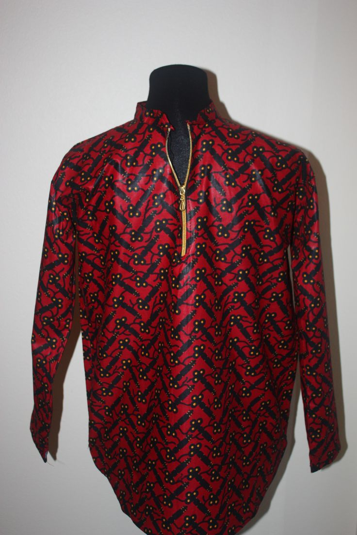 This men's long sleeve shirt has a front zipper and is made of African cloth. Red with a black and yellow pattern. Shirt is 20 inches across and 28 inches long, with 21 inch sleeves. Hand crafted by the Lulu mamas in Uganda.  These men's shirts are so unique! Each shirt is sewn by a Lulu mama or daughter trained in tailoring through the Lulu program. They are made from beautiful African cloth, and each shirt has special details that blend traditional African design with the creative vision…