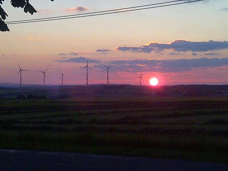 Sun setting behind wind turbines in Gattendorf, Germany