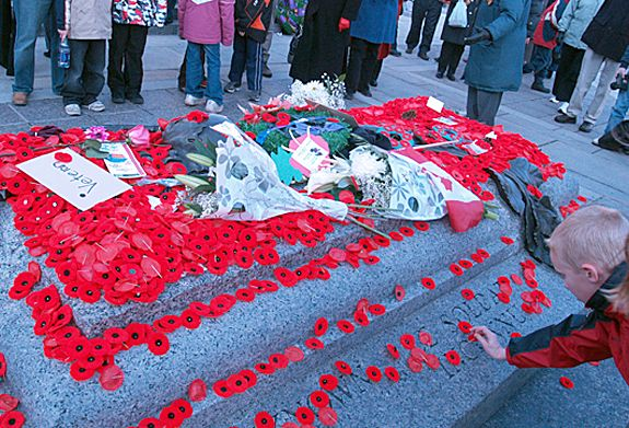 A child placing poppy on the Tomb of the Unknown Soldier