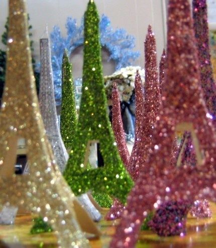 Cut out the paper Eiffel Towers and use spray glue, then glitter... voila!