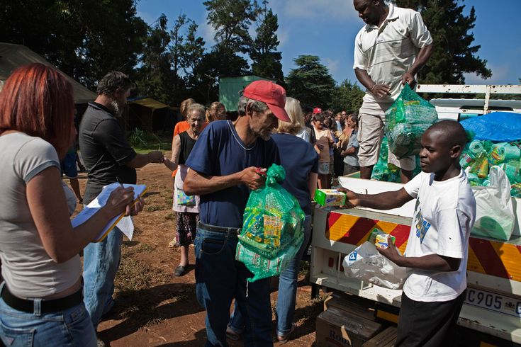 A man receives a monthly supply of food aid donated to residents of a squatter camp for poor white South Africans at Coronation Park in Krugersdorp on March 6, 2010. (REUTERS/Finbarr O'Reilly)