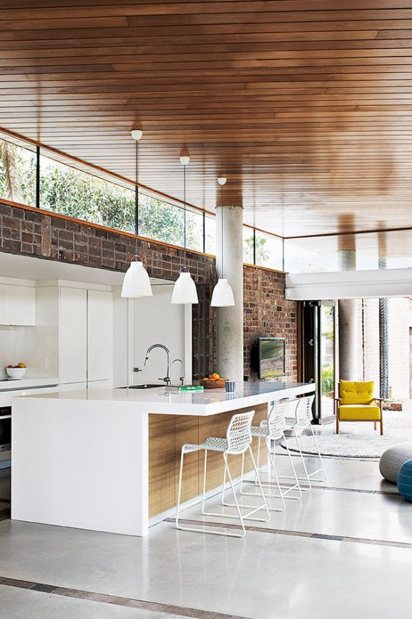 Modern kitchen featuring wood, a white palette and hanging pendant lights.