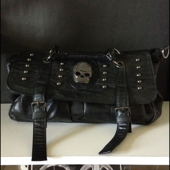 Black leather skull satchel bag Satchel style black leather purse. Faux leather. Lots of pockets. 2 exterior, larger interior zipped divider, smaller zip pocket and duo pocket on opposite side. Damask print lining. Cross body strap. Skull and studs on front flap. Magnetic button closure. Bags Crossbody Bags