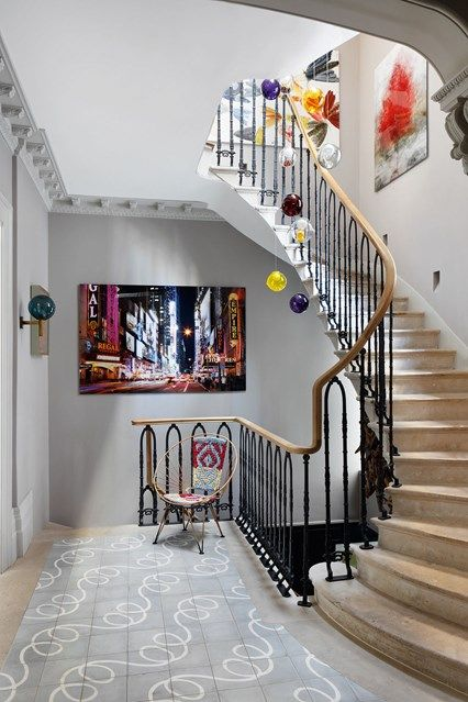 In this hallway a contemporary, coloured glass pendant light from Bocci above the Portland stone staircase.