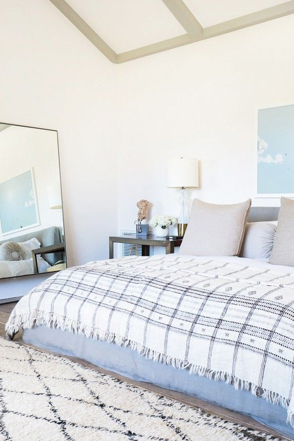 White bedroom with neutral plaid bedding, leaning mirror: