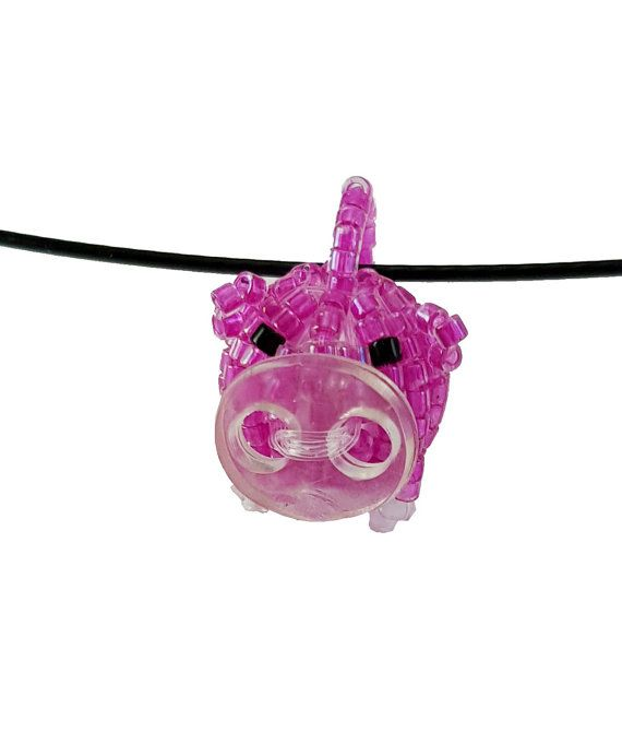 Small Pig Beaded Bead Doll Necklace  I was inspired by a Japanese bead book for this unique little Piggie!!  Medium: Pendant bead work Size: 3/4 inch tall and a half inch wide Fit: One size fits most Colors: Black, pink, and red seed beads and a clear button Comes with: A black wire necklace  This piece takes a few hours to complete. The body is a beaded bead.   This pendant can be taken off of the wire and put on another necklace.
