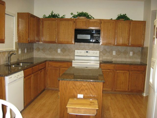 Honey oak cabinets what color countertop what color for Black kitchen walls