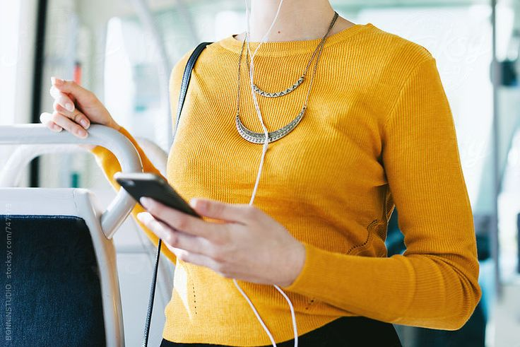 Closeup of a woman using her smartphone standing in the train. by BONNINSTUDIO for Stocksy United