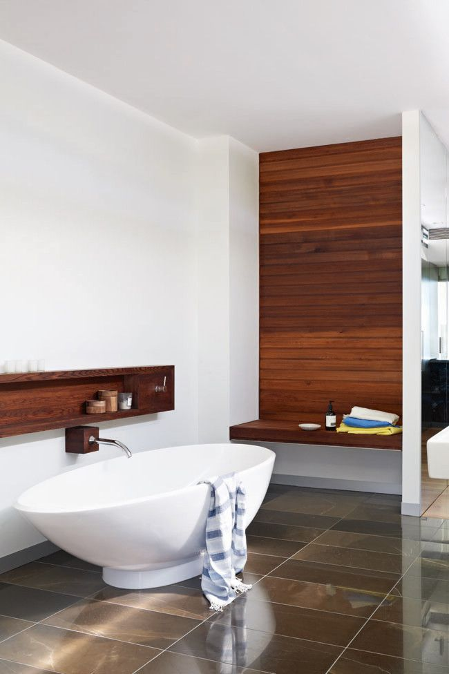 Beautiful large, brown tiles, separate bathtub, wooden shelves and wall feature with white walls and decor.