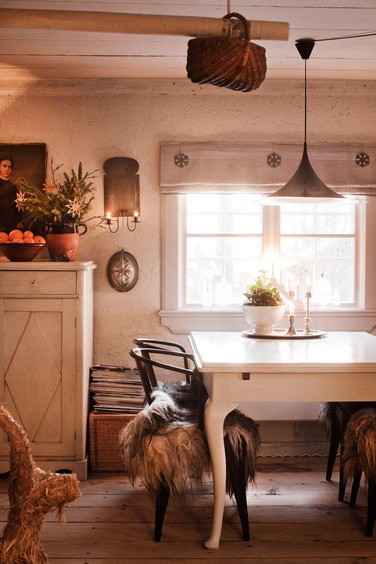 STÄMNINGSFULLT OCH TRADITIONELLT - HÄR VILL MAN FIRA JUL: Bocken har sin plats i köket och skvallrar om juletid, tillsammans med granris, halmpynt, apelsiner och ljusstaken i fönstret. Stålstolarna från Jerners rum, har försetts med värmande fårskinn. Skänken är 1880-tal liksom målningen ovanför. Taklampa Semi, formgavs 1968 och tillverkas idag av Gubi | Sköna Hem