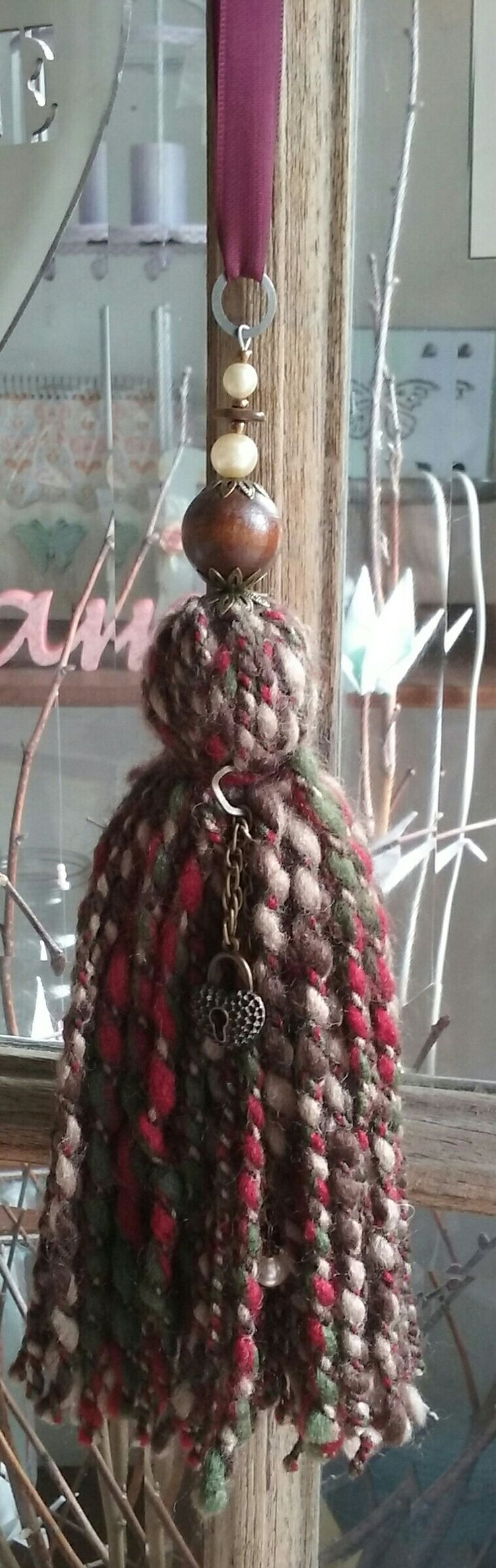 Borla de lana en tonos bordeaux con dijes colgante. Sujeta cortina o puertero