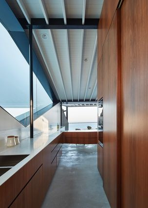 Wrapping around the pantry/storage core, the kitchen bench leads from the more intimate family room to the main living area, revealing the ocean view.