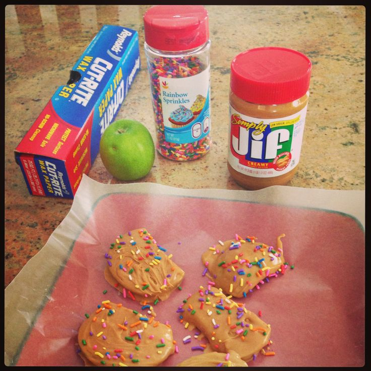 Heat bowl of peanut butter in microwave for 30 seconds, smother the peanut butter over apple slices, top with sprinkles and allow to harden.