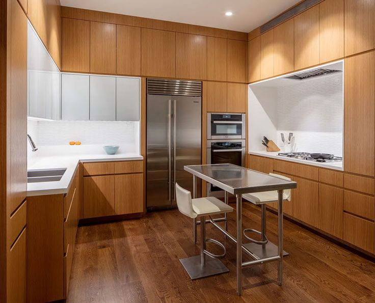 In this U-shaped modern kitchen, wood cabinets are broken up by white countertops, tiles and additional cabinets. A small stainless steel island ties in with the stainless steel appliances.