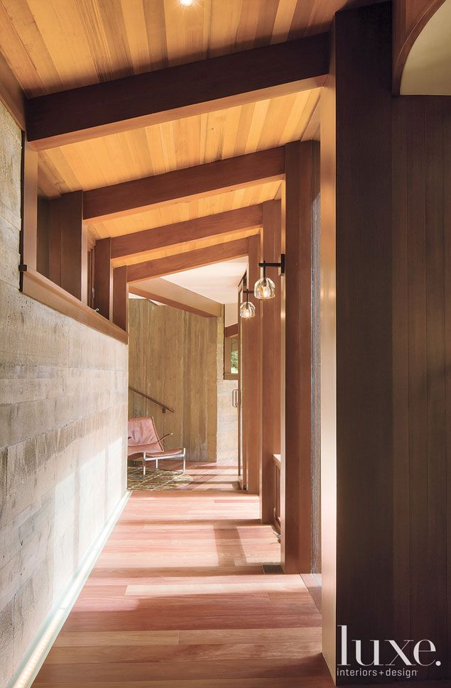 A hallway, marked by a poured-concrete wall and bronze- and-crystal sconces from Alison Berger Glassworks, leads to a library area off the m...